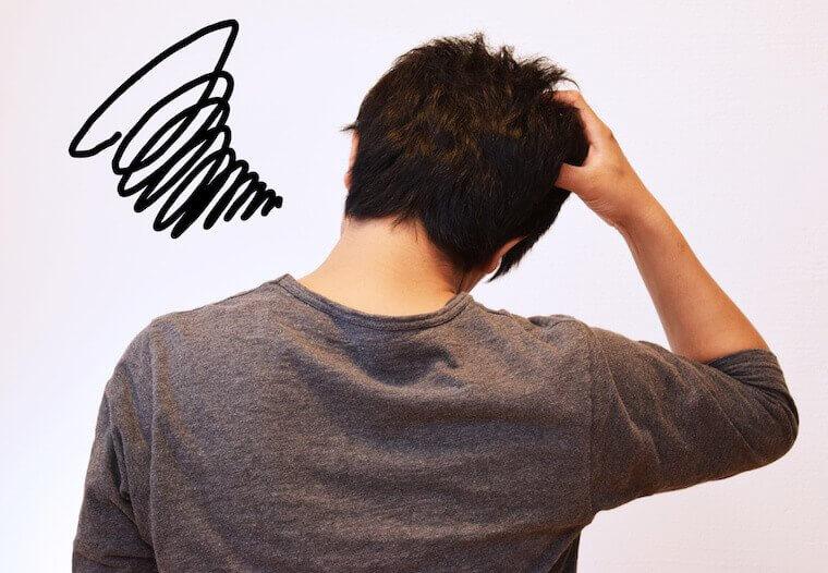 頭を抱える後ろ姿の男性